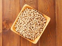 Seque grãos-de-bico crus na bacia de madeira no fundo rústico do marrom escuro, vista superior fotos de stock