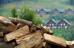 Seque la leña tajada en tallo sobre las cabañas en la foto de la acción de la colina de la montaña Foto de archivo libre de regalías