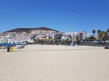 Seque la opinión de playa arenosa en los las Américas Tenerife de Playa de con los apartamentos en la distancia fotos de archivo
