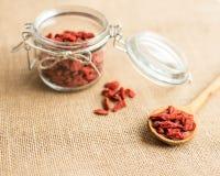 Seque las bayas rojas del goji en cuchara de madera en el fondo rústico para una dieta sana Fotografía de archivo