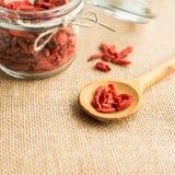Seque las bayas rojas del goji en cuchara de madera en el fondo rústico para una dieta sana fotos de archivo libres de regalías