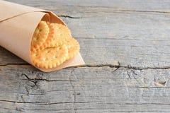 Seque las galletas saladas en un documento de embalaje sobre un fondo de madera del vintage con el espacio de la copia para el te Imagenes de archivo