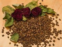 Seque las rosas rojas en las semillas del café y el fondo de madera Fotografía de archivo