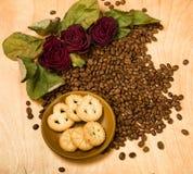 Seque las rosas rojas y las galletas en las semillas del café Imagenes de archivo