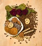 Seque las rosas rojas y las galletas en las semillas del café Imágenes de archivo libres de regalías