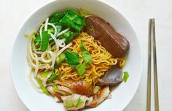 Seque os macarronetes de ovo chineses que cobrem a carne do pato e o broto de feijão na bacia e em hashis inoxidáveis Fotos de Stock