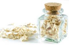Seque a raiz de aipo esmagada na garrafa de vidro e em um montão isolado Imagens de Stock Royalty Free