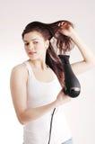 Sequedad blanca hermosa de la muchacha su pelo con un hairdr Foto de archivo libre de regalías
