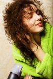 Sequedad de la mujer su pelo con el hairdryer Foto de archivo libre de regalías
