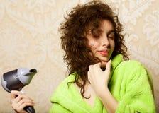 Sequedad de la mujer su pelo con el hairdryer Imágenes de archivo libres de regalías