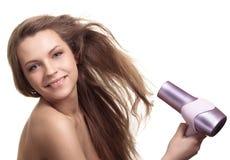 Sequedad de la mujer su pelo con el hairdryer Imagen de archivo