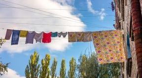 Sequedad de la ropa interior en la cuerda entre las casas viejas Imagen de archivo libre de regalías