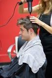 Sequedad femenina del peluquero su pelo masculino del cliente Imagen de archivo libre de regalías