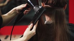 Sequedad profesional del pelo en salón de belleza Peluquero que usa el secador de pelo moderno almacen de video