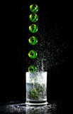 Ball sequence falling into a water glash. Sequence of green ball falling into a water glash and splashes Royalty Free Stock Photos