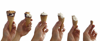 Sequence of an ice cream being eaten step by step. Man`s hand holding a chocolate covered vanilla ice cream cone with peanut Royalty Free Stock Photos