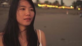 Sequence of young beautiful and happy Asian Korean woman having sweet relaxed walk in the beach on sunset evening smiling natural stock footage