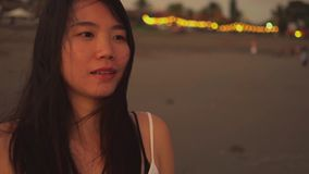 Sequence of young beautiful and happy Asian Korean woman having sweet relaxed walk in the beach on sunset evening smiling natural. Enjoying the beauty of stock footage