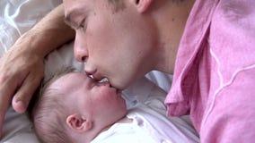 Sequenza del movimento lento del padre Kissing Baby Daughter a letto video d archivio