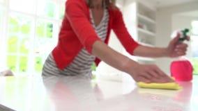 Sequenza del movimento lento della superficie di pulizia della donna in cucina stock footage