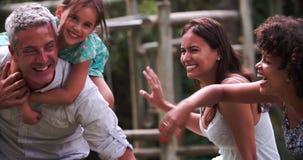 Sequenza del movimento lento delle famiglie che giocano insieme nel giardino video d archivio