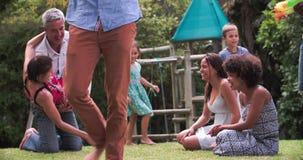 Sequenza del movimento lento delle famiglie che giocano insieme nel giardino stock footage