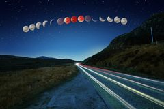 Sequenza eccellente di eclissi della luna del sangue blu e tracce dell'automobile Fotografia Stock