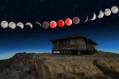 Sequenza eccellente di eclissi della luna del sangue blu e una vecchia casa abbandonata Immagini Stock