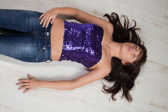 Sequined. Girl with a sequined top lying on the ground royalty free stock images