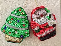 Sequined holiday ornaments. Kitschy sequined Christmas tree and Santa holiday ornaments stock image