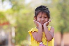 Ser asiatiska barn för flicka kameran och klubban Arkivfoto