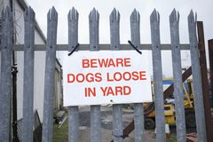 Ser cuidadoso cães frouxamente no sinal da jarda em trilhos do metal para a segurança imagens de stock