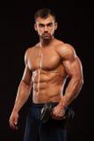 Ser den idrotts- mannen för stilig makt med hanteln säkert framåtriktat Stark kroppsbyggare med sex packe, perfekt abs Royaltyfri Foto