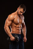 Ser den idrotts- mannen för stilig makt med hanteln säkert framåtriktat Stark kroppsbyggare med sex packe, perfekt abs Arkivfoto