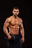 Ser den idrotts- mannen för stilig makt med hanteln säkert framåtriktat Stark kroppsbyggare med sex packe, perfekt abs Arkivfoton