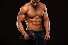Ser den idrotts- mannen för stilig makt med hanteln säkert framåtriktat Stark kroppsbyggare med sex packe, perfekt abs Royaltyfri Bild