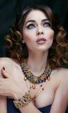 Ser den rika kvinnan för skönhet med lyxiga smycken som moget slut upp, ljus makeup arkivbild