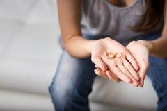 Ser esposa triste olha o anel na palma na frente dele, nostálgico sobre um marido anterior, família, união O conceito da Imagens de Stock