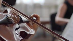 Ser humano com jogos da curva no fim de madeira do violino acima no concerto da sinfonia video estoque