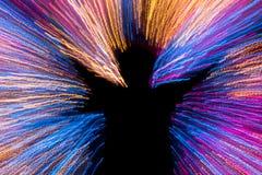 Ser humano con forma alegre en la iluminación del multicolor Fotos de archivo libres de regalías