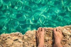 Ser humano despido com os pés descalços no penhasco da rocha pronto para saltar Fotos de Stock Royalty Free