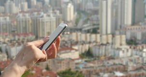 ser humano 4k que usa um smartphone contra o fundo urbano moderno da construção vídeos de arquivo