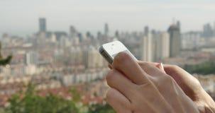 ser humano 4k que usa un smartphone contra fondo urbano moderno del edificio almacen de metraje de vídeo