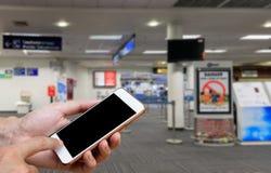 Ser humano que sostiene la pantalla en blanco del teléfono elegante y que espera salidas Fotografía de archivo libre de regalías