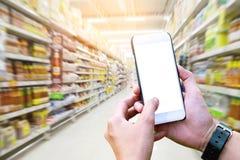 Ser humano que usa el teléfono móvil con la pantalla en blanco en los grandes almacenes b Imágenes de archivo libres de regalías