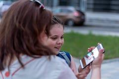 Sera di estate feste Foto piacevole dell'orologio della figlia e della madre sullo smartphone fotografia stock