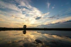 Sera di estate sul lago con la riflessione del cielo nell'acqua Immagine Stock