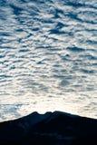 Sera di inverno del paesaggio della montagna della siluetta con il cloudscape fantastico immagine stock