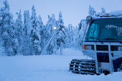 Sera di inverno ed il gatto delle nevi sull'orlo della foresta Immagini Stock