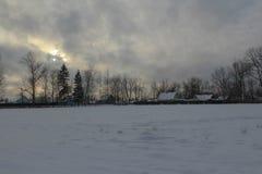 Sera di inverno nel villaggio Gli insiemi del sole, nuvole, freddo, buio del gelo immagini stock